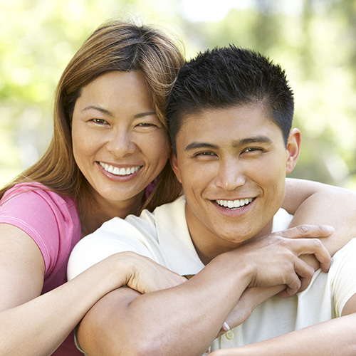 Attractive young couple smiling with their arms around each other