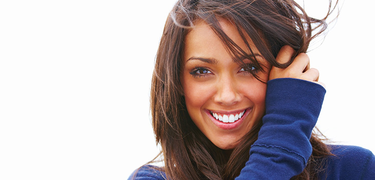 Smiling woman wearing a blue sweater and brushing her hair back in the wind