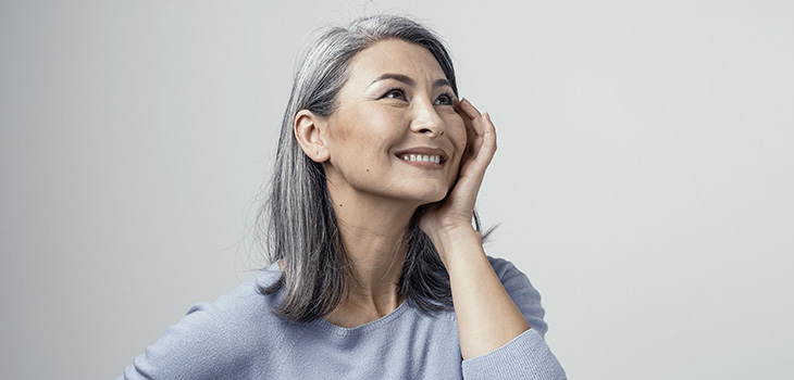 Smiling woman looking off into the distance while wearing a light blue sweater