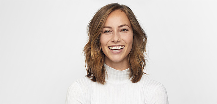 Young woman smiling while she is wearing a white mock turtleneck sweater