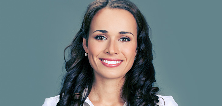 Smiling woman with long brown hair and dark brown eyes