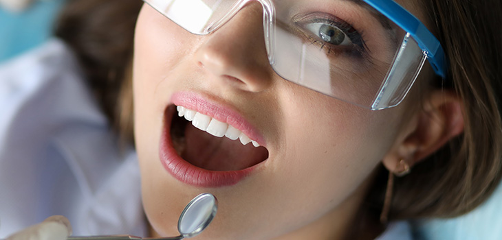 Female patient wearing eye shields getting an exam
