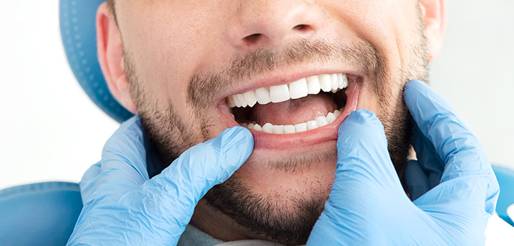 Dentist using their gloved hands to pull down the patient's lower lip and look at their teeth