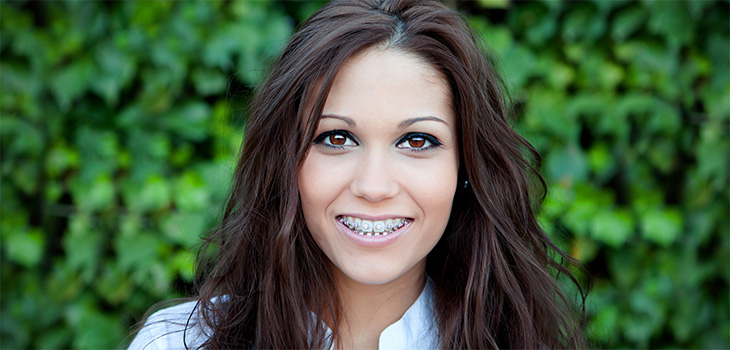Young woman with brown hair and eyes standing outside smiling with pink braces on her teeth