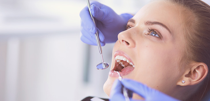 Close up photo of a woman having her teeth examined