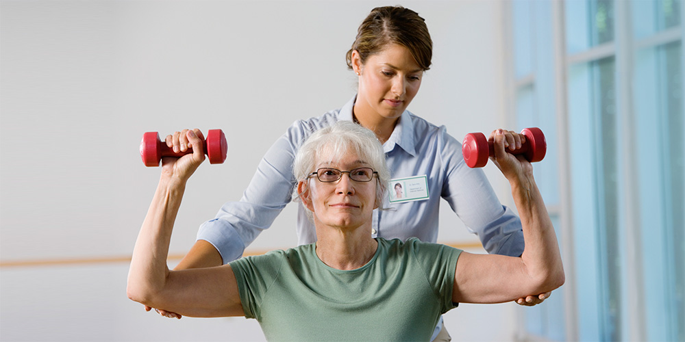 nurse helping woman lift weights