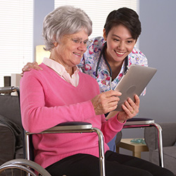 nurse and resident in wheelchair looking at results on an ipad while smiling