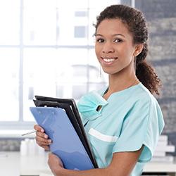 nurse smiling holding paperwork