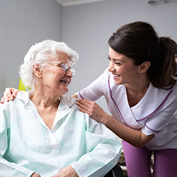 nurse talking to resident in a wheelchair