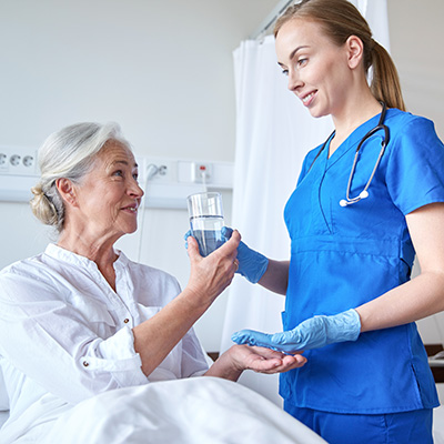 nurse helping woman with medication