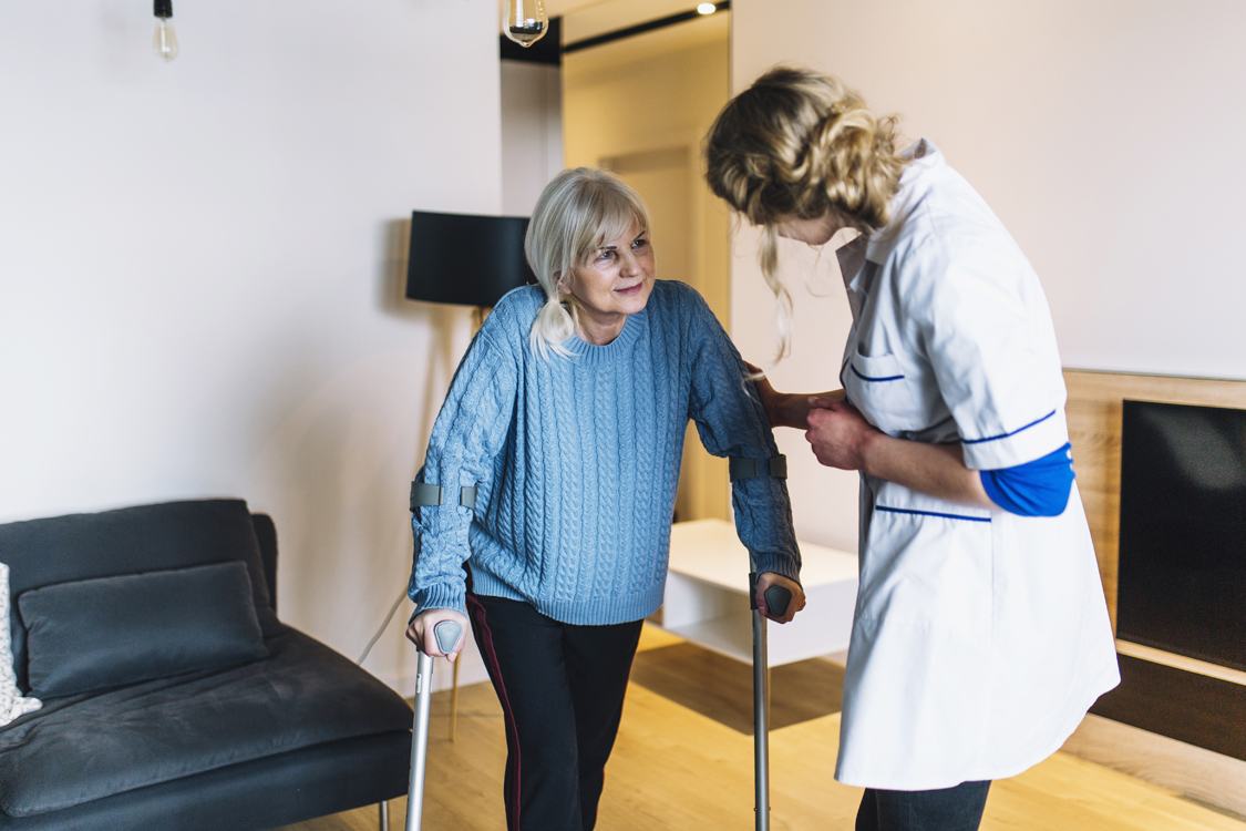 doctor helping woman on crutches