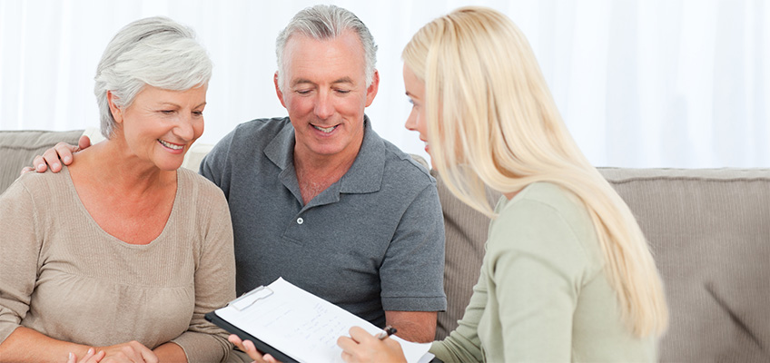 A woman going over paperwork with a couple.
