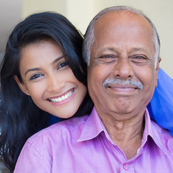 A daughter and father smiling outside.