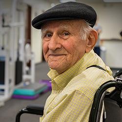 A senior in a wheelchair smiling.