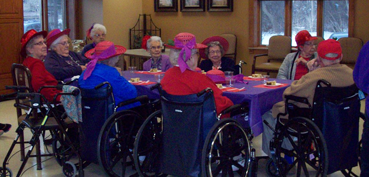 residents in wheelchairs sitting around a table