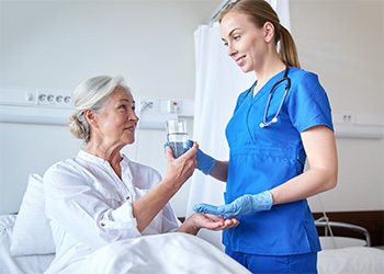 nurse giving a resident water