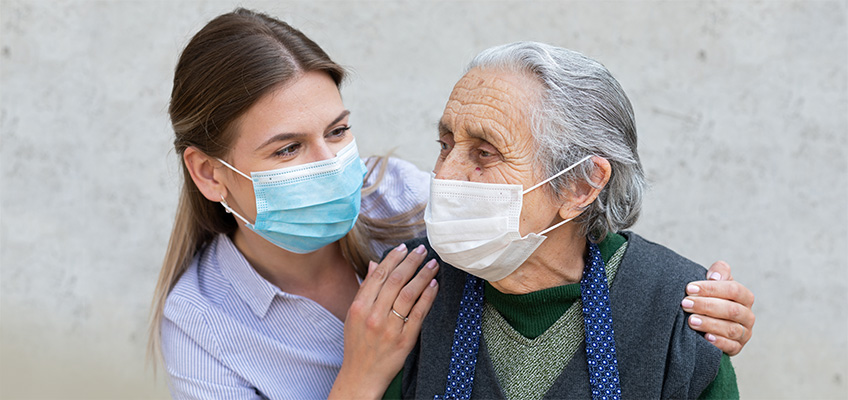 A family member visiting a loved one with masks on.