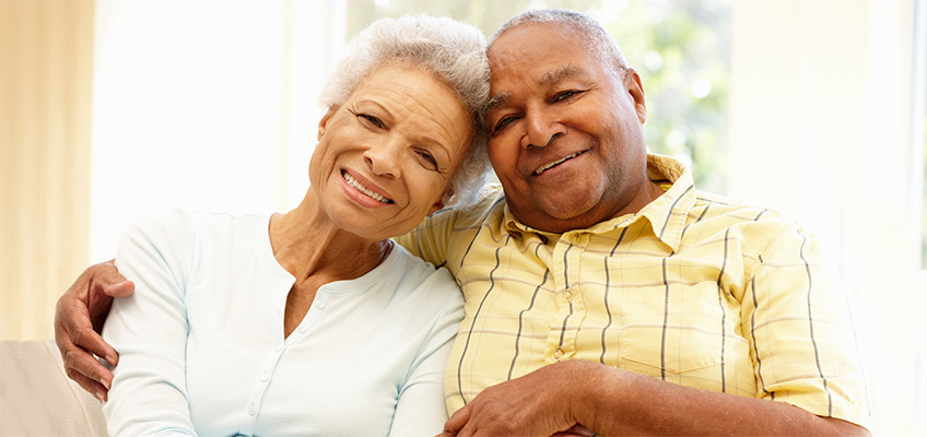 elderly couple embracing each other on the couch