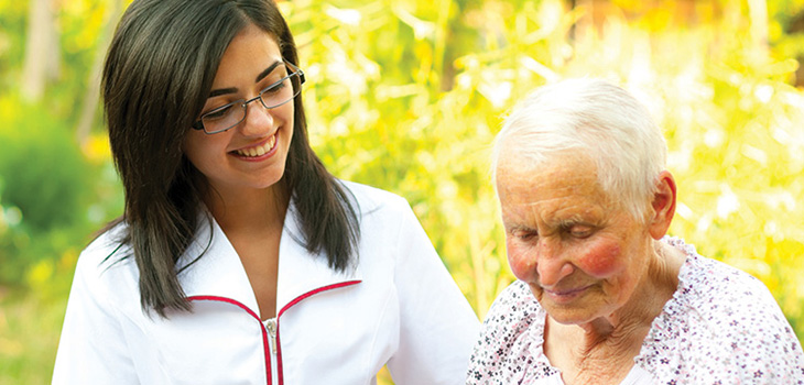 nurse and elderly woman standing together