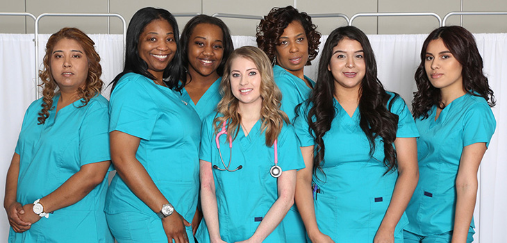 Several nursing dressed in blue scrubs gathered together