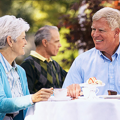 Couple dining outside with dessert and coffee on the table