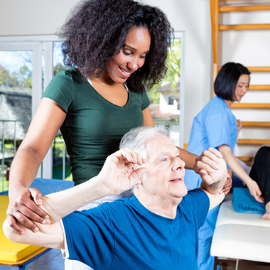 Occupational therapist helping man stretch