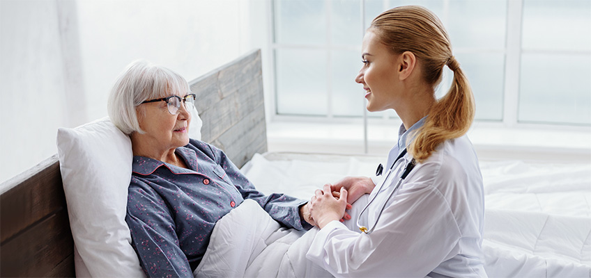 Doctor checking in on a patient and holding her hand