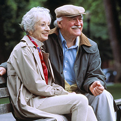 Smiling couple seated outside on a bench
