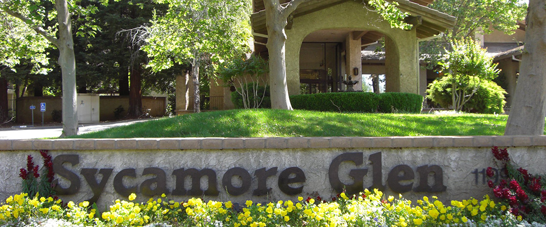 Sycamore Glen sign with yellow flowers and front portico