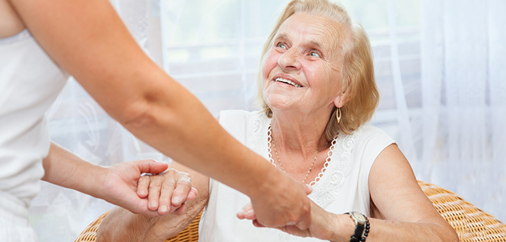 A woman holding the hands of a senior woman helping her up.
