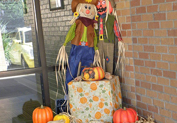 Scarecrow with pumpkins outside the entrance to the building.