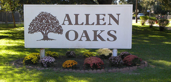 Allen Oaks sign out front with flowers underneath it.