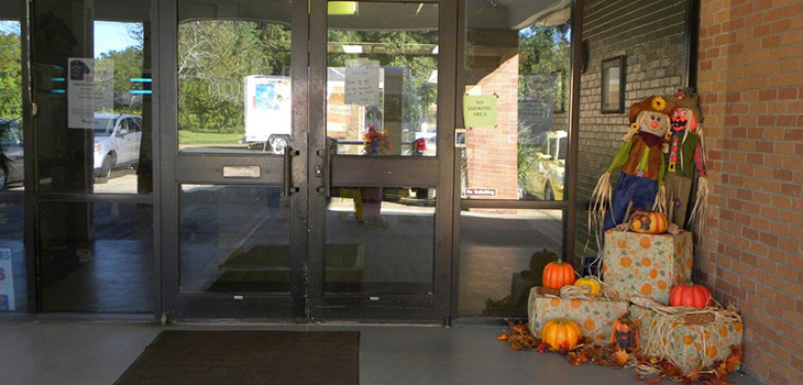 The entrance to the building with scarecrows and pumpkins outside.