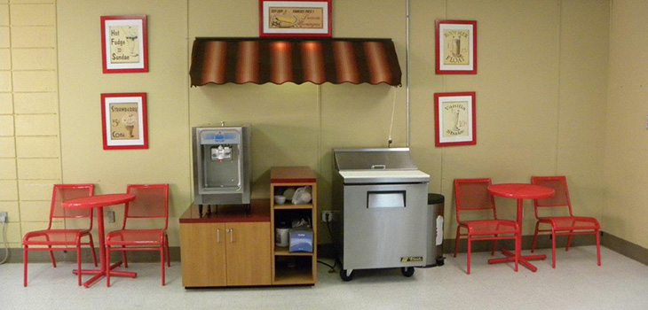 A cafe with a popcorn maker and ice cream area.