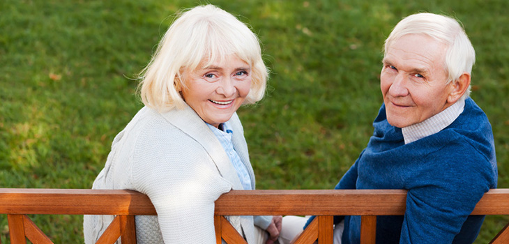 couple smiling and seated on a bench outside