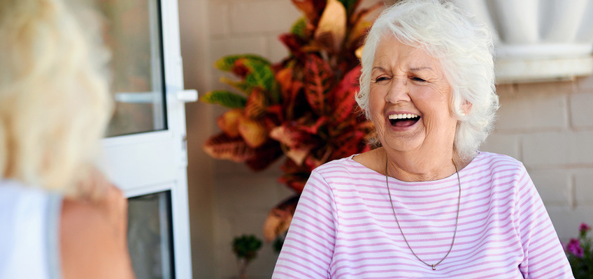 elderly woman in a striped shirt laughing
