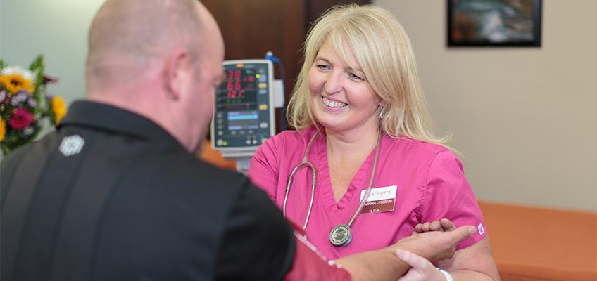 nurse and resident smiling taking blood pressure