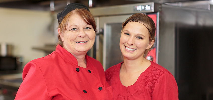 two smiling chefs wearing red