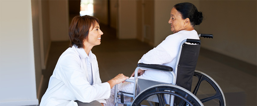 A doctor kneeling down talking to a patient in a wheelchair