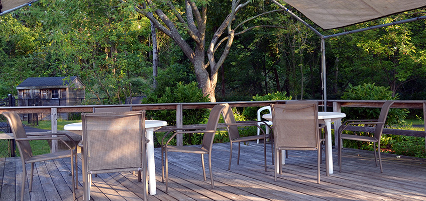 Covered outside patio area on a deck with a beautiful view of lush, tall trees