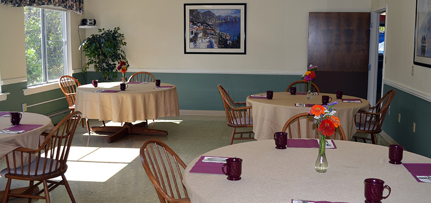 Resident dining room with cloth table covers, place settings and flowers in the middle of the tables