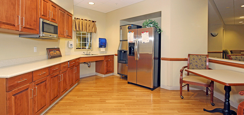 A communal area with seating, a refrigerator, shelving, and microwave