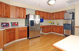 A room with refrigerator, cabinets and ice maker