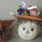 A handmaid pumpkin with hair, a hat and painted face