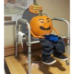 A pumpkin head on a chair