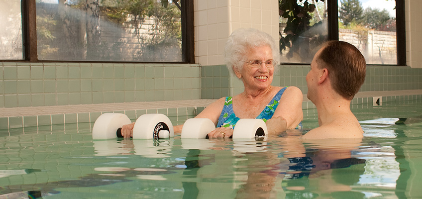 A staff member assisting a resident with aqua therapy