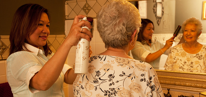 A resident having her hair done in the salon