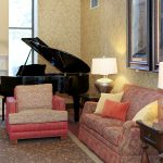 Lobby area with high vaulted ceiling, grand piano, fireplace and comfortable seating