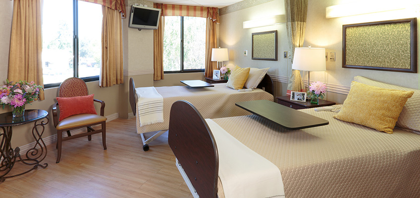 Double occupancy resident room with nicely made beds and flowers on each side table