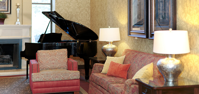 Lobby area with grand piano, fireplace and comfortable seating